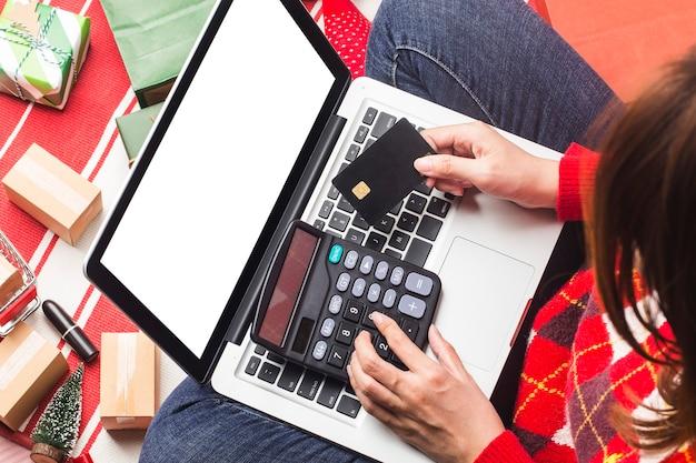 Achats en ligne de noël une acheteuse avec un ordinateur portable se prépare à la veille de noël