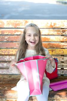 Achats. petite fille heureuse avec un grand sac à provisions rose