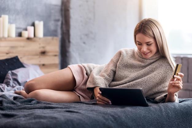 Achats pour le plaisir. jolie jeune femme blonde couchée dans son lit et à l'aide de tablette lors de vos achats en ligne.