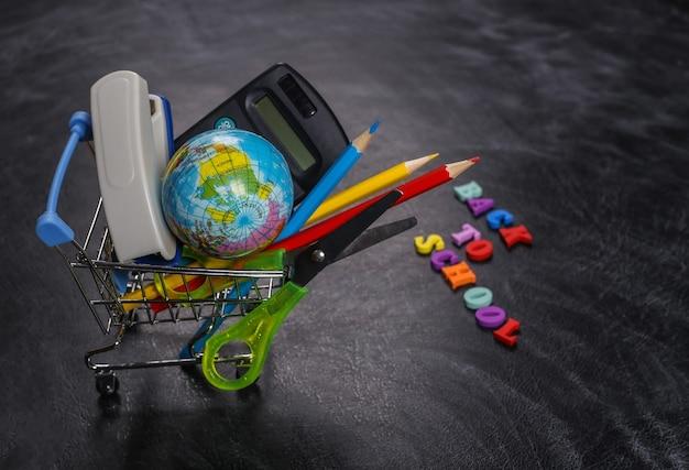 Achats préscolaires. chariot de supermarché avec fournitures scolaires sur un tableau noir avec le texte retour à l'école
