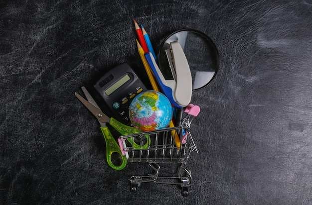 Achats préscolaires. chariot de supermarché avec fournitures scolaires sur un tableau noir. vue de dessus