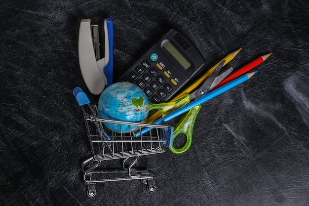 Achats préscolaires. chariot de supermarché avec fournitures scolaires sur un tableau noir.