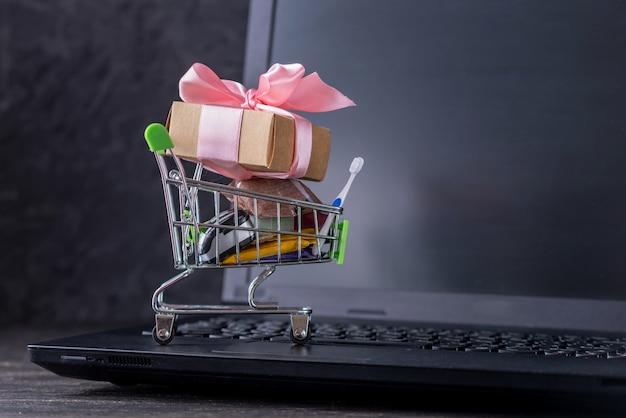 Achats quotidiens et cadeaux dans le panier sur le clavier de l'ordinateur portable