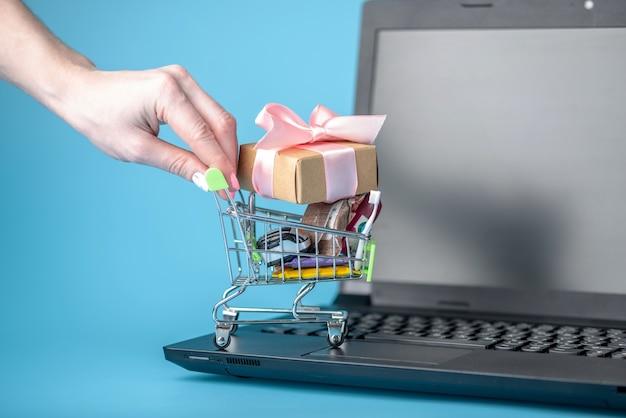 Achats quotidiens dans le panier sur le clavier de l'ordinateur portable sur fond bleu