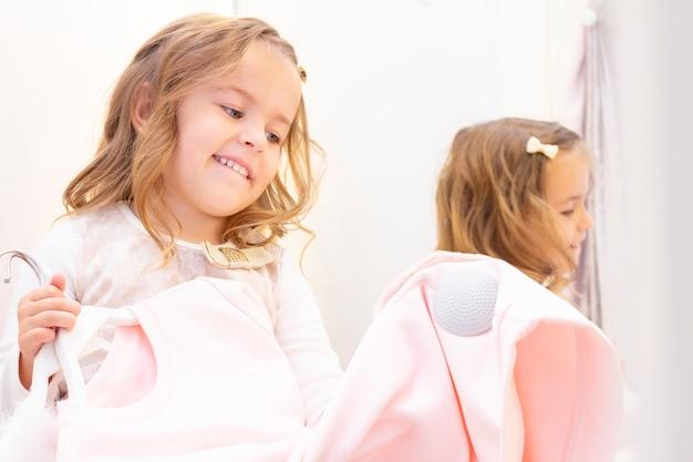 Achats. remises. petite fille accro du shopping. fille essayant une belle robe doucement rose dans la cabine d'essayage de la boutique. centre commercial, shopping. émotions