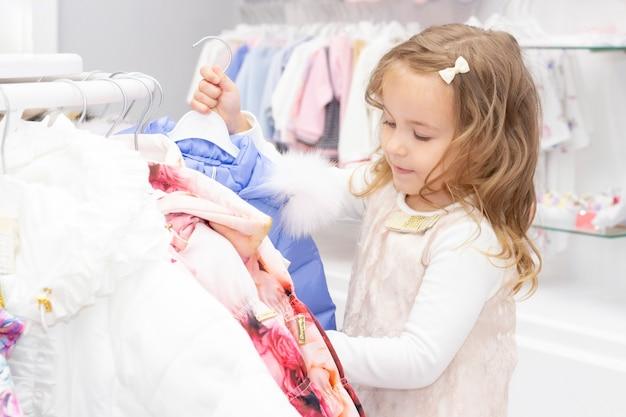 Achats. remises. petite fille accro du shopping. fille ravie de belles vestes, choisit des vêtements chauds. centre commercial, shopping. émotions