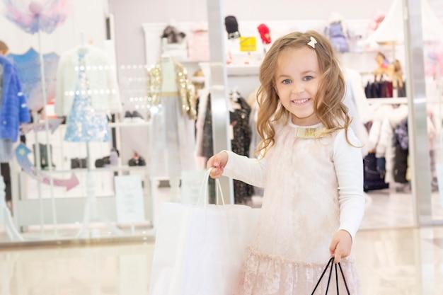 Achats. remises. petite fille accro du shopping. fille avec des sacs en mains. sacs blancs avec fond. le plaisir du shopping. centre commercial, shopping. émotions