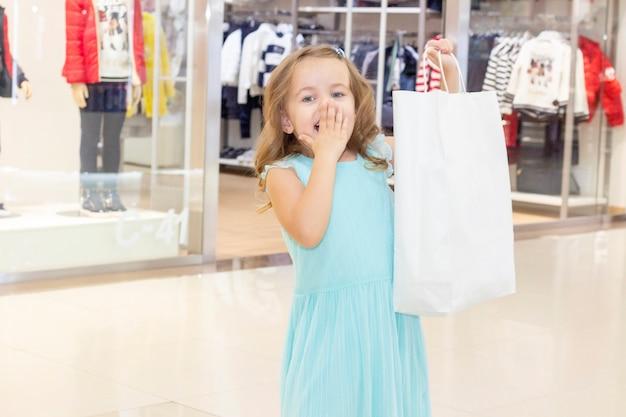 Achats. remises. petite fille accro du shopping. fille avec des sacs à provisions en mains. fond de sacs blancs. centre commercial, shopping. émotions