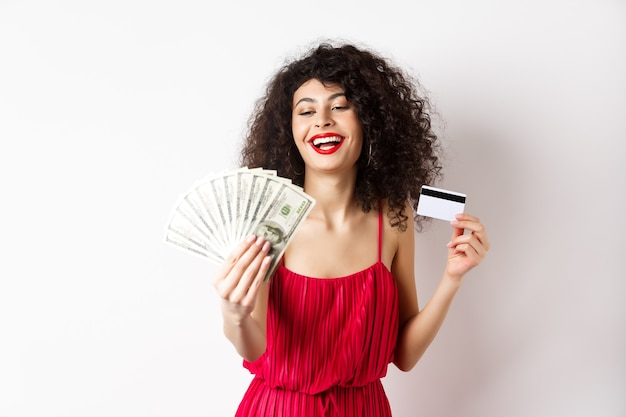Achats. riche femme prospère aux cheveux bouclés et robe rouge, tenant une carte de crédit en plastique et à la satisfaction de billets d'un dollar, fond blanc.