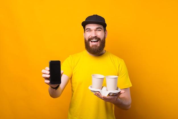 Acheter du café en ligne, homme montrant un smartphone et tenant une tasse de café en papier sur jaune