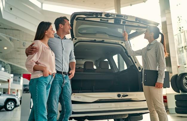 Acheter leur première voiture ensemble. jeune vendeuse de voitures debout chez le concessionnaire racontant les caractéristiques de la voiture aux clients.