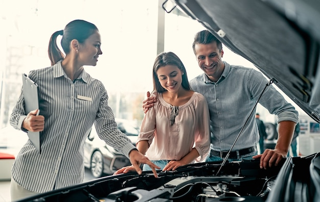 Acheter leur première voiture ensemble. jeune vendeuse de voitures debout chez le concessionnaire, racontant les caractéristiques de la voiture sous le capot aux clients.
