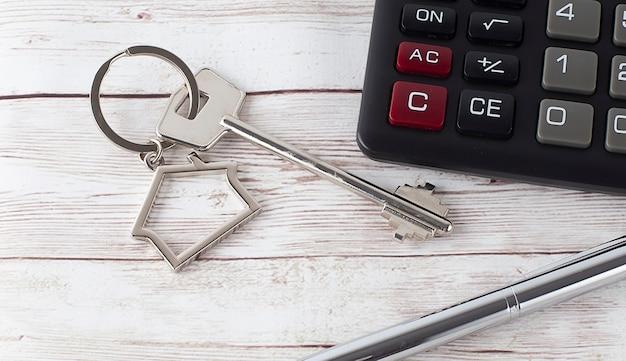 Acheter une maison ou un concept d'hypothèque. touches avec calculatrice et plan sur le fond en bois.