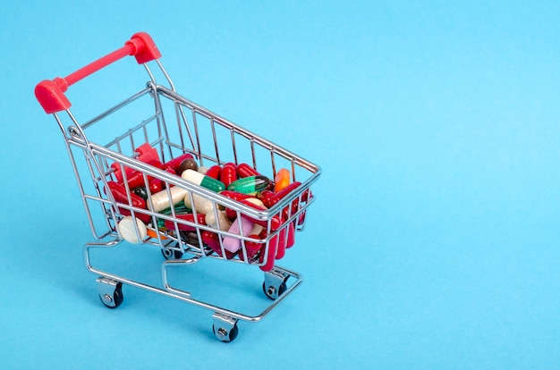 Acheter des médicaments, panier avec divers médicaments, pilules, comprimés sur fond bleu.