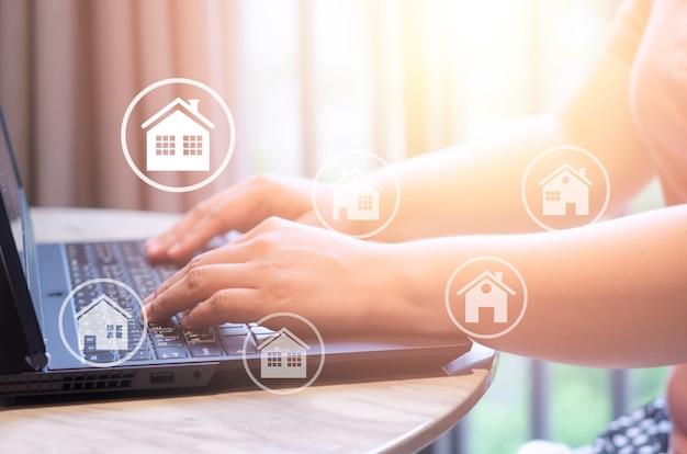 Acheter, vendre et louer des maisons ou un concept immobilier, propriété en ligne, mains tapant sur un ordinateur portable en arrière-plan