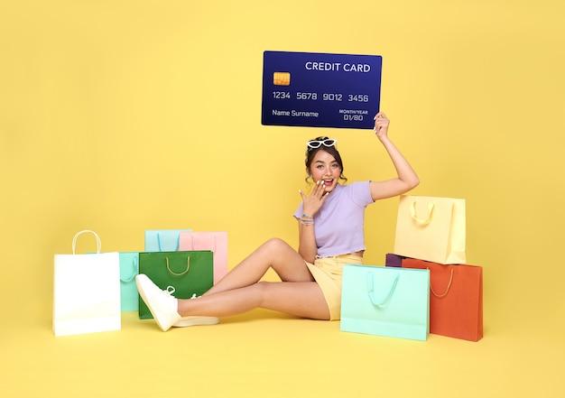 Acheteur de belle femme asiatique adolescent assis avec des sacs à provisions et tenant la carte de crédit dans les mains sur fond jaune.