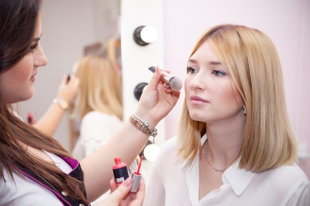 Acheteur de belle fille, maquilleuse, visagiste appliquant le testeur de poudre sur le visage sur le miroir. annonce décoratif professionnel magasin de cosmétiques, studio de maquillage