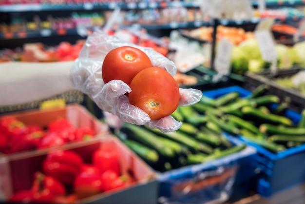 L'acheteur en gants choisit des légumes lors d'une pandémie en raison d'un nouveau virus dangereux, le coronavirus