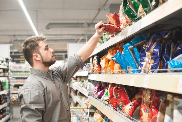 L'acheteur porte une chemise et achète une collation dans un supermarché.