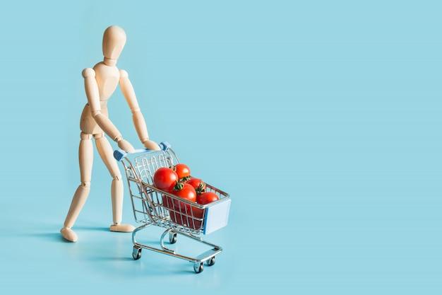 Acheteur en poupées en bois avec chariot de courses et tomates.
