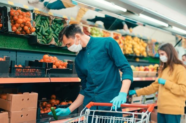Les acheteurs portant des masques de protection choisissent des fruits au supermarché. coronavirus en ville