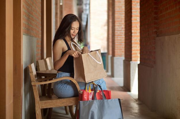 Une acheteuse assise et vérifiant ses marchandises dans un sac à provisions avec des sacs à provisions sur le sol