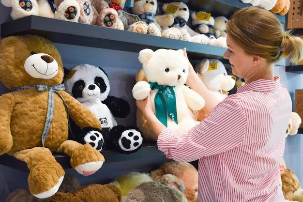 Achetez des peluches. l'acheteur choisit le jouet. une femme achète un ours en peluche. cadeau pour enfant