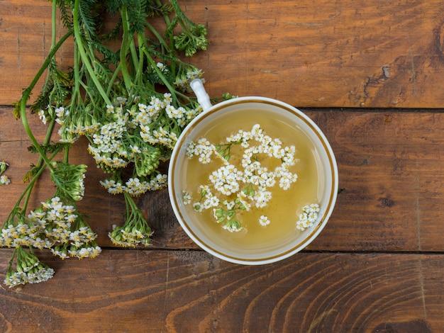 Achillée millefeuille, une tasse avec une décoction de fleurs d'achillée millefeuille sur un fond en bois