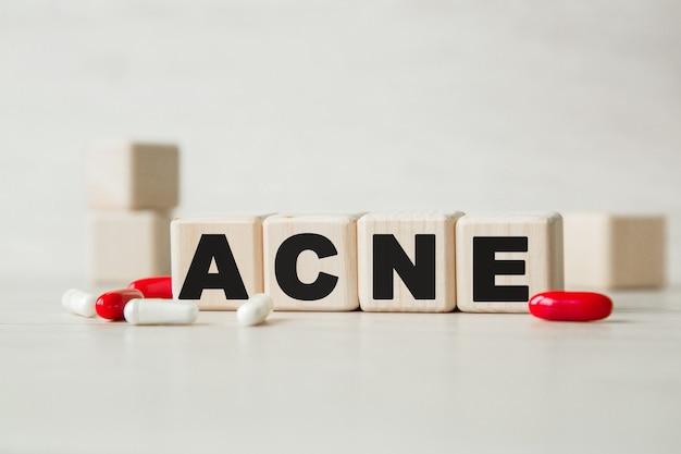 Acné. le mot écrit sur des cubes, des pilules . concept médical