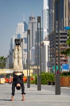Acrobat garde l'équilibre entre les mains avec le paysage urbain flou de dubaï. concept de possibilité moderne, commerciale et illimitée.