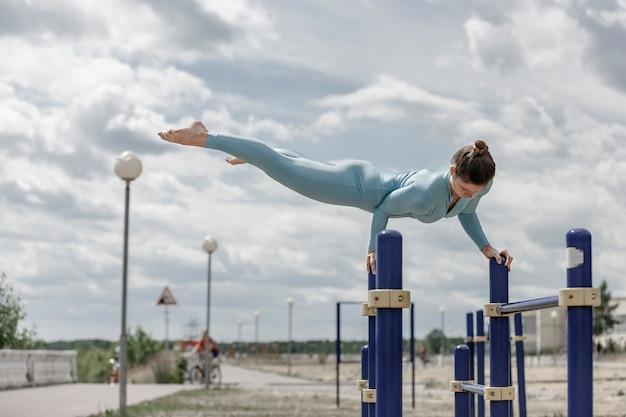 Acrobate fille en costume bleu sur une barre horizontale