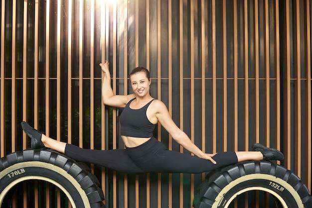 Une acrobate flexible pose en arrière-plan du mur restant sur d'énormes roues. une sportive heureuse regarde la caméra et sourit.