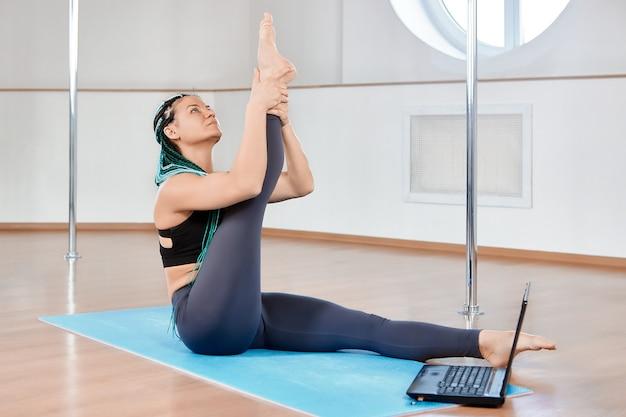 Acrobaties au sol ou en parterre dans une salle de fitness femme mature faisant des étirements en suivant les instructions