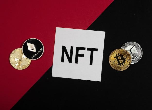 Acronyme nft sur papier note sur fond rouge et noir avec des pièces de crypto-monnaie