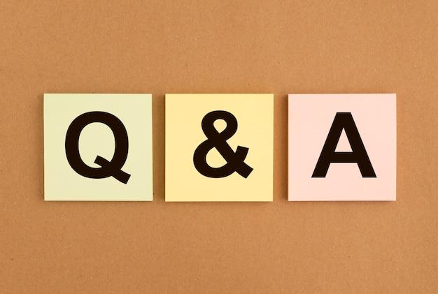 Acronyme qa sur des notes autocollantes sur un tableau marron. qna mot. notion q. questions et réponses.