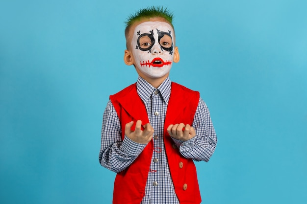 L'acteur fait peur avec ses doigts. joyeux halloween. garçon en costume sur mur bleu avec espace libre.