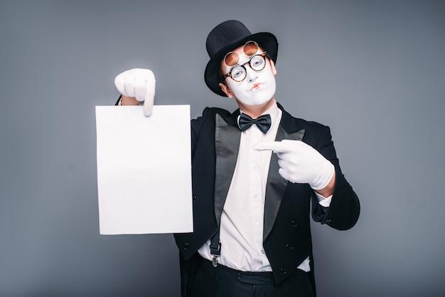 Acteur de mime masculin avec feuille de papier vide. pantomime en costume, gants, lunettes, masque de maquillage et chapeau.