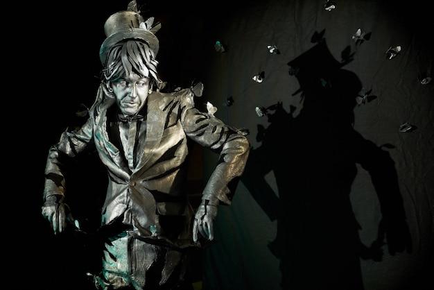 Acteur de mime professionnel faisant une expression faciale surprise et regardant des papillons, fabriqués à partir de papier et peints en bronze, qui volent autour.pantomimiste posant à la caméra pendant le processus de création