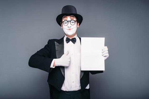 Acteur de pantomime jouant avec une feuille de papier vide. comédie mime en costume, gants, lunettes, masque de maquillage et chapeau