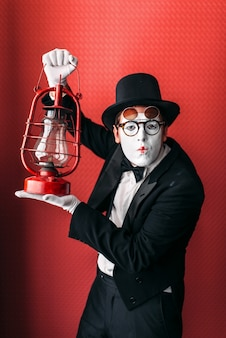 Acteur de pantomime avec lanterne au kérosène. comédie mime en costume, gants, lunettes, masque de maquillage et chapeau. comédien homme avec lampe à huile vintage