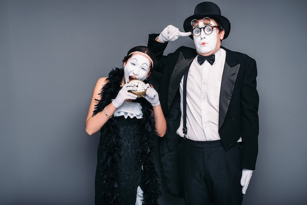Les acteurs de mime effectuent, l'actrice grignote un réveil. artistes de théâtre de pantomime