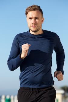 Actif jeune homme sportif qui court en plein air