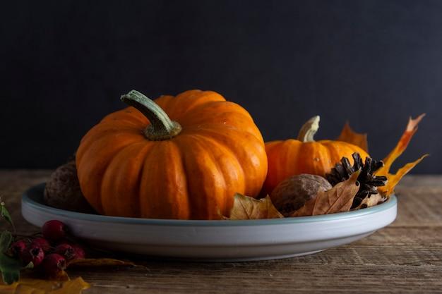 Action de grâce et automne avec citrouille orange dans une assiette en bois rustique