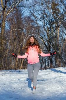 Active jeune femme effectue un exercice avec une corde à sauter