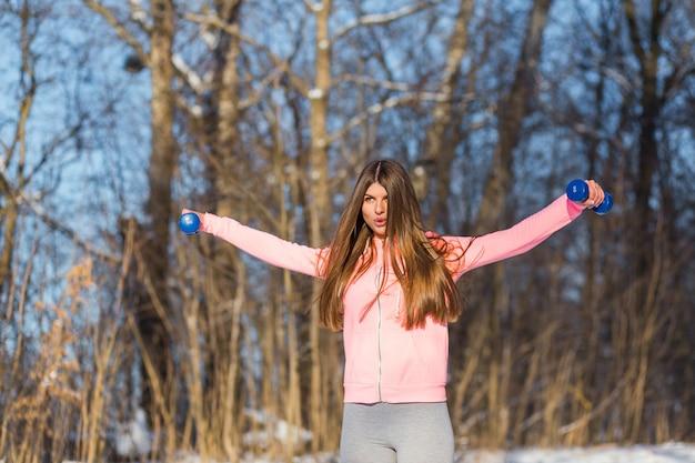 Active jeune femme effectue un exercice avec un haltère