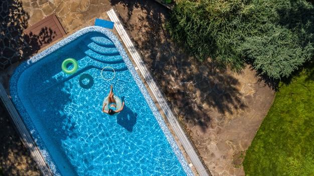 Active jeune fille dans la piscine vue aérienne de dessus, enfant se détend et nage sur l'anneau gonflable beignet et s'amuse dans l'eau en vacances en famille, tropical resort de vacances