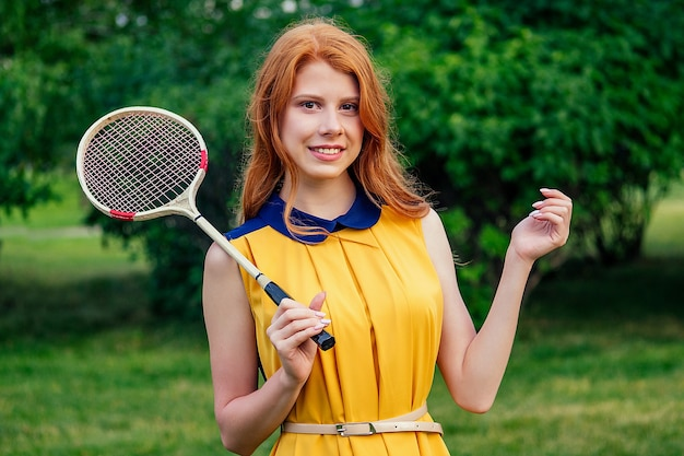 Active joyeuse belle jeune femme norvégienne irlandaise rousse au gingembre dans une robe jaune et dans une raquette de tennis rose jouant au badminton dans le parc d'été