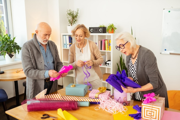 Activité agréable. personnes âgées joyeuses se tenant ensemble tout en s'amusant à emballer leurs cadeaux