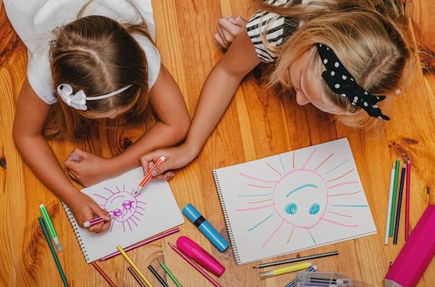 Activité de loisirs en intérieur. la sœur aînée aide à dessiner un soleil sur sa petite sœur. vue de dessus.