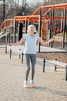 Activité préférée. corde à sauter joyeuse femme mince tout en exerçant en plein air